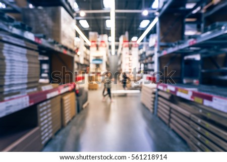 Blurred Customers Shopping In Large Furniture Warehouse With Forklift,  Cart. Row Aisle, Bins