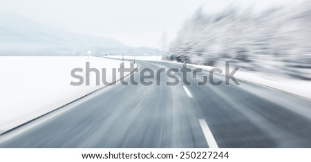 Blurred danger and fast turn at the icy snow road. Motion blur visualizies the speed and dynamics. - stock photo