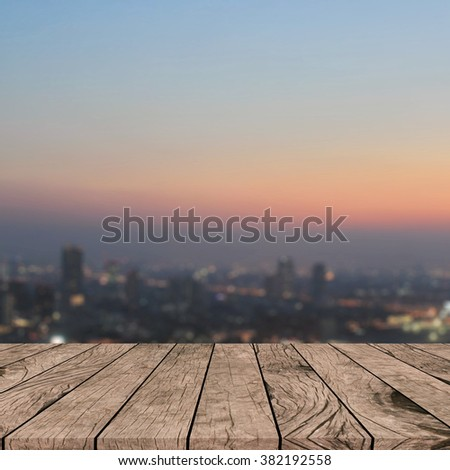 Blurred dark night city background with wood panels perspective.blur downtown skyline backdrop concept.blurry urban sunset/sunrise hours wallpaper with wood tiles stripe floorboard for montage display
