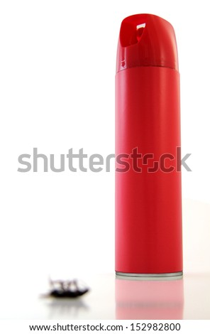 Blurred, dead bug in front of a tall, red  can of bug spray. - stock photo