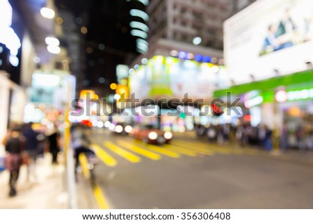 Blurred defocused abstract background of traffic and people walking on zebra crossing - Crowded Nathan Road street in Hong Kong city center during rush hour in urban business area - stock photo