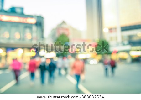 Blurred defocused background of people walking on Auckland city streets - Abstract bokeh of crowded Queen Street in New Zealand capital at rush hour - Vintage filter and slight tilted composition - stock photo