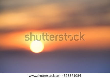 Blurred defocused background of sunset at the sea - Abstract bokeh of sun going down through the clouds over the horizon - Emotional concept of deep connection with nature wonders - stock photo