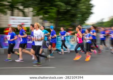 Blurred (defocused) image of marathon runners. - stock photo