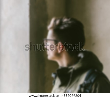 Blurred defocused young man looking through a window - stock photo