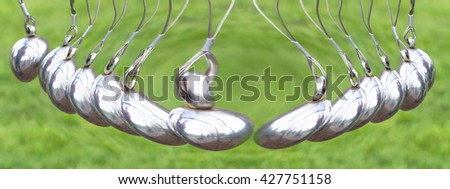 Blurred desirable. Artistic work of my own.  Newton's Cradle or pendulum ball, Newton pendulum also called Newton's cradle. Physics is action, reaction and concept or cause and effect. - stock photo