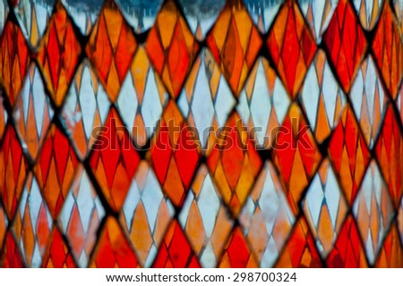 blurred detail of multicolored stained glass with irregular diamond block pattern