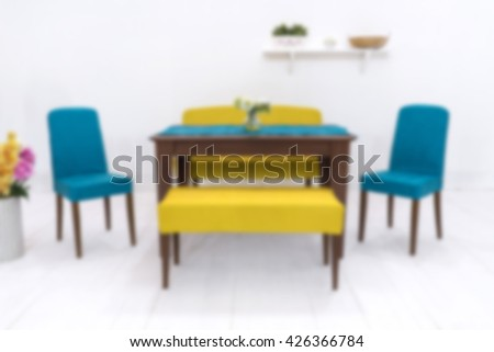 blurred dining table and comfortable chairs in modern home with elegant table setting - stock photo