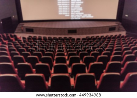 Blurred empty red cinema seats from back top row.