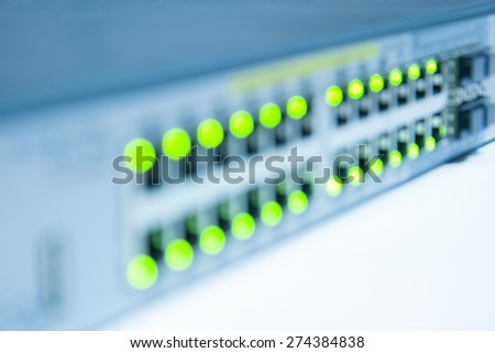 Blurred ethernet network switch with LED flashing isolated on white background - stock photo