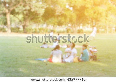 blurred family sit on grass field in the park - stock photo