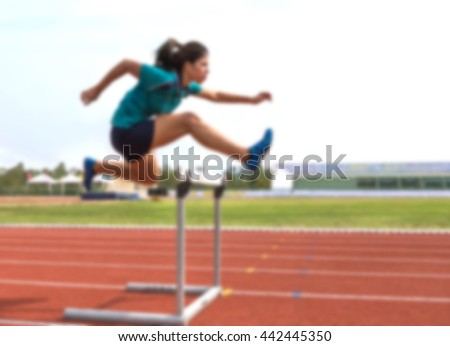 blurred female jump over hurdle during training  - stock photo