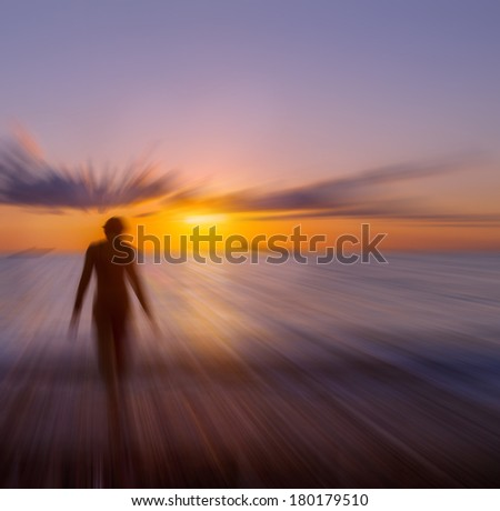 blurred figure of a girl on a background of the sea and sunset sky - stock photo