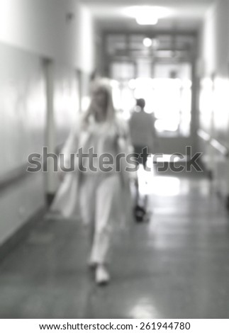 blurred figures of doctors and nurses in a hospital corridor - stock photo