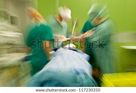 Blurred figures of doctors in medical uniforms performing brain surgery on patient - stock photo