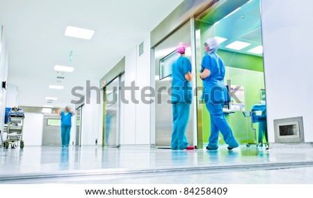 blurred figures wearing medical uniforms in hospital surgery corridor - stock photo