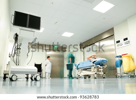 Blurred figures with medical uniforms moving patient in hospital corridor - stock photo