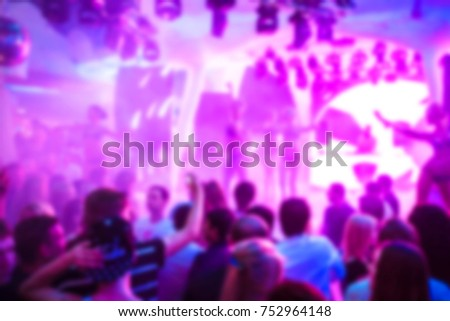 Blurred for background. club party. Night club dj party people enjoy of music dancing sound with colorful light with Smoke Machine and lights show. Hands up in earth.