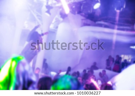 Blurred for background Night club dj party people enjoy of music dancing sound with colorful light with Smoke Machine and lights show. Hands up in the earth.