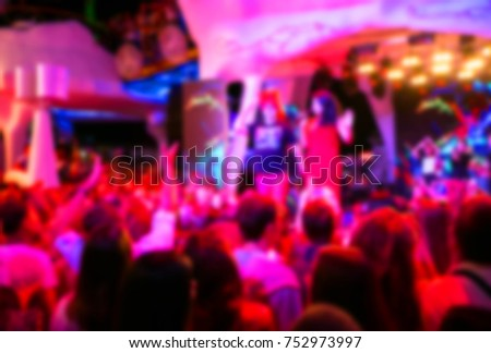 Blurred for background. night club party. Night club dj party people enjoy of music dancing sound with colorful light with Smoke Machine and lights show. Hands up in earth
