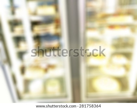 Blurred fridge with cakes in bakery shop - stock photo
