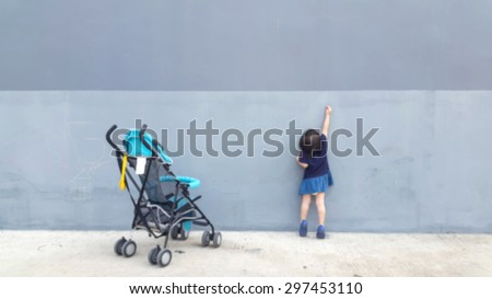 Blurred girls down from the cart. She is currently writing on the wall imagination. For blur background. bright tone - stock photo