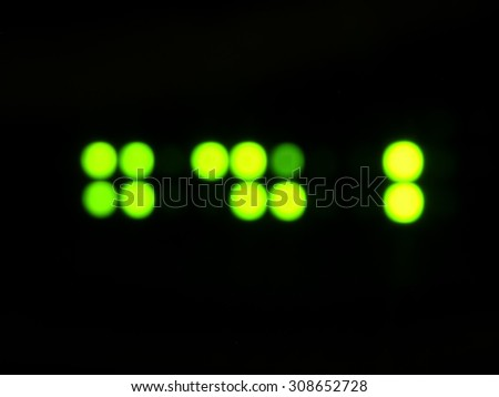 blurred green LED flashing circles on a black background