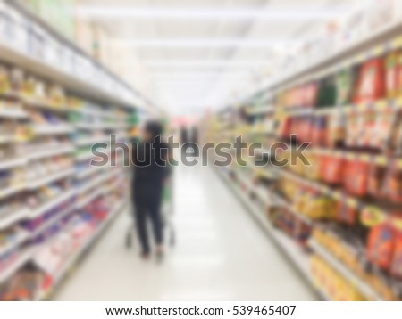 blurred group asian housewife woman choosing products on shelves in supermarket:blur people checking price of goods on weekend day concept:blur girl shopping/buying at local market center on vacation