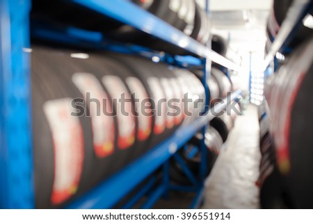 Blurred group of new tires for sale at a tire store - stock photo