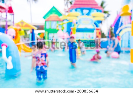 Blurred happy chiidren has fun playing in water fountains in water park  - stock photo