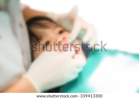 blurred image A dentist curing little girls teeth - stock photo