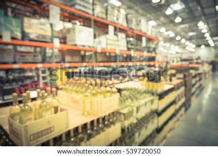 Blurred image aisle of bottles in wine section of modern distribution warehouse. Defocused of storehouse interior aisle and rows. Inventory, logistic, export. Beverage alcohol background. Vintage look