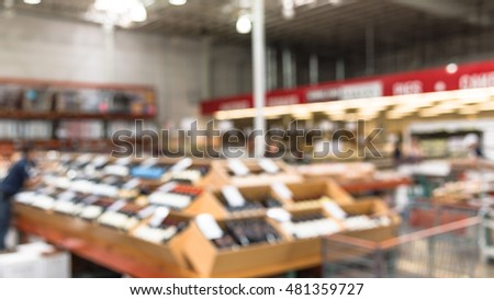 Blurred image aisle of bottles in wine section of modern distribution warehouse with customers choosing wine. Inventory, logistic, business, wholesale, export concept. Beverage alcohol background.