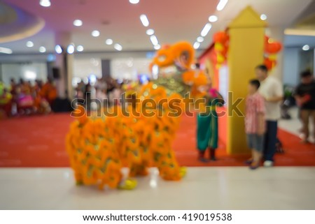 Blurred image background of Chinese traditional dancing lion ,Image of lights Dragon blur in Chinese New Year,Traditional colorful chinese lion, Chinese paper means,on red background.vintage color - stock photo