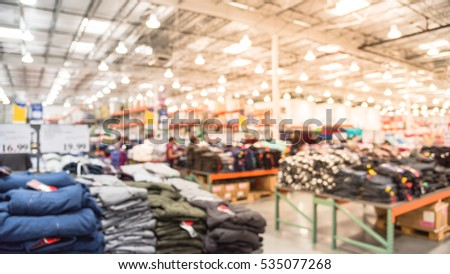 Blurred image huge variety of items at clothing section in modern distribution warehouse. Defocused background of storehouse interior aisle and row. Inventory, logistic, export concept. Panorama style