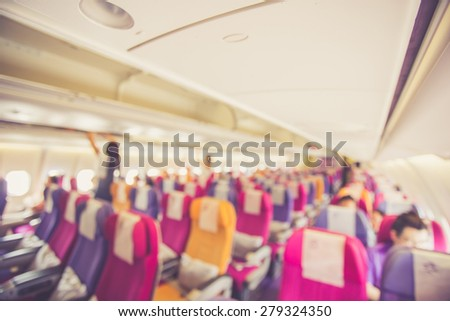 Blurred image Interior of airplane with passengers on seats, retro filter effect - stock photo