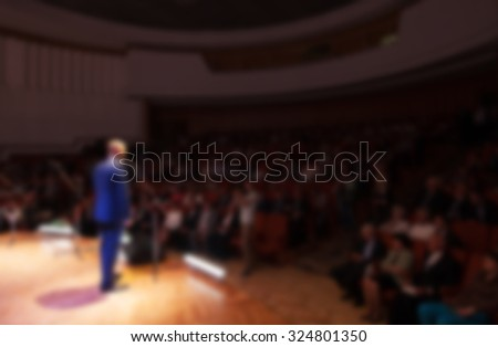 blurred image of a businessman giving a presentation in a conference/meeting - stock photo