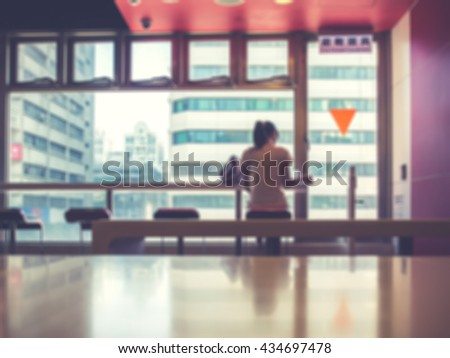Blurred image of a girl sitting in restaurant reading. People in restaurant background. People reading. Toned image.