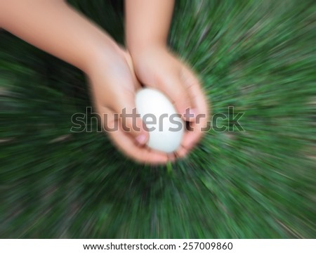 blurred image of a kid holding eggs - stock photo