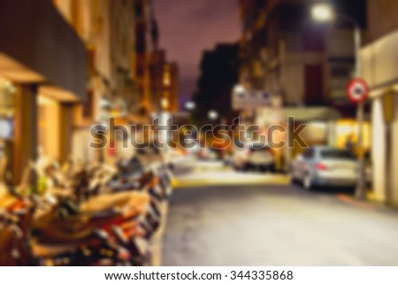 Blurred image of a lane parked with motorcycles and cars in city at night. Night city background. Toned image.