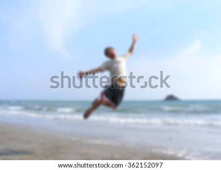 Blurred image of a man jumping at the beach .