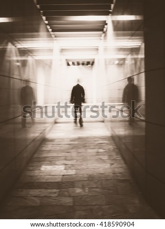 Blurred image of a man walking in an underground passage. Man walking away in a under passage to the light. Monochrome image. Motion blur. - stock photo