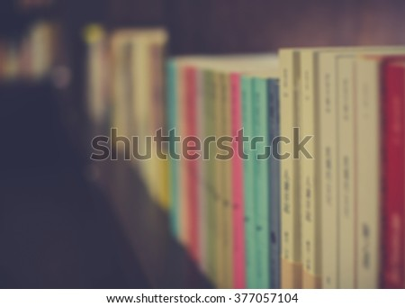 Blurred image of a row of books on shelf in a bookstore. Close up of books on shelf. Bookstore background. Retro effect.
