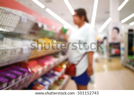 Blurred image of a woman with shopping cart  in the grocery store.
