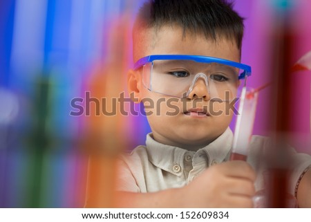 Blurred image of a young researcher dropping in the test-tube on the foreground - stock photo