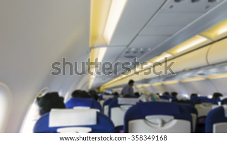 Blurred image of airplane interior / cabin with passengers on-board