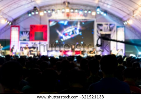 blurred image of Audience enjoying music in front of concert stage, noise added