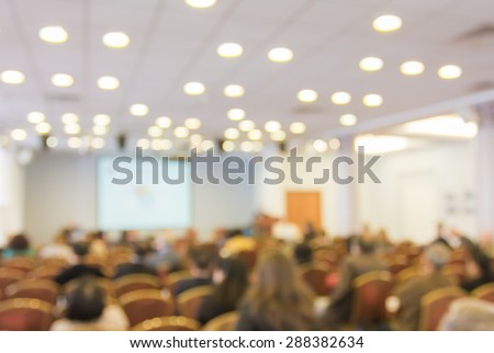 Blurred image of audience people in hall or auditorium with screen, blur background - stock photo