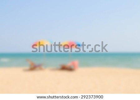 Blurred image of beach chair and umbrella on sand beach - stock photo