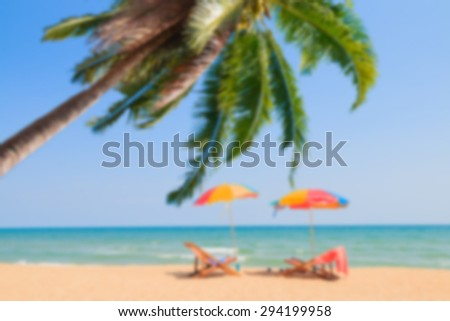 Blurred image of beach chair with coconut tree and umbrella on sand beach - stock photo